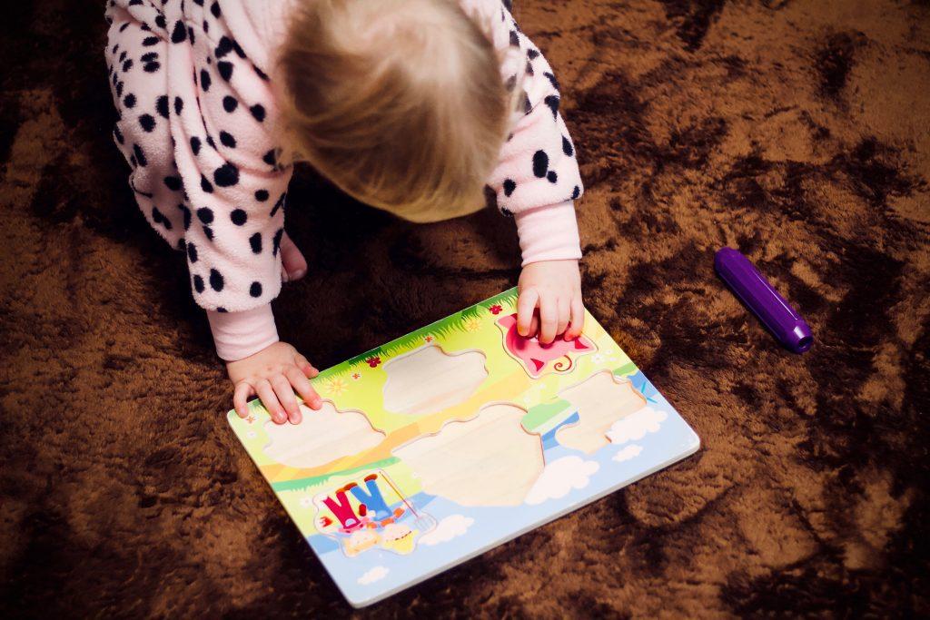 Na foto uma menina montando um quebra-cabeças em cima de um tapete.