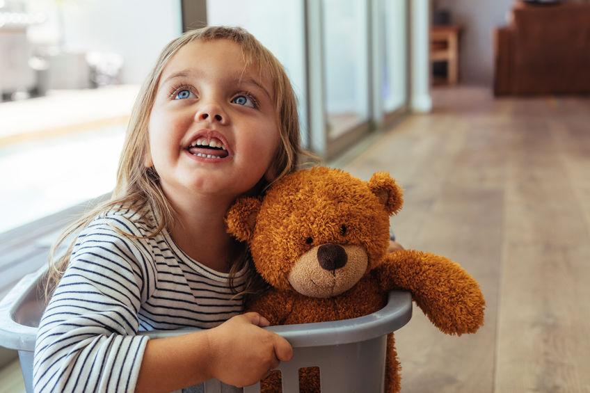 Na foto uma menina com um ursinho dentro de um cesto de roupas.