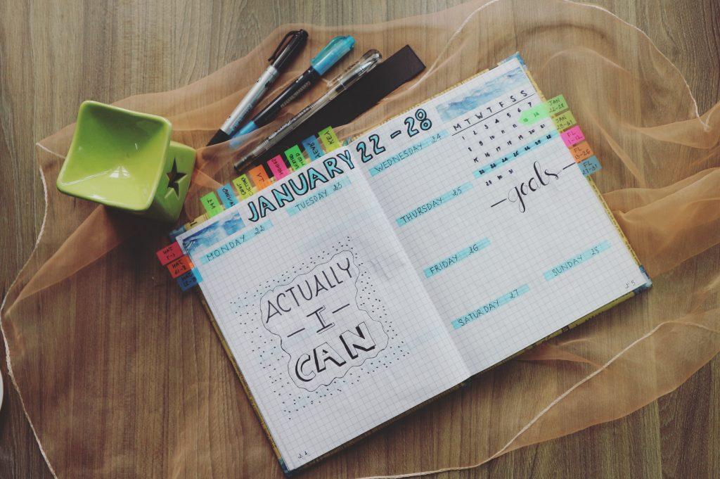 Na foto uma agenda com marcadores e algumas canetas.