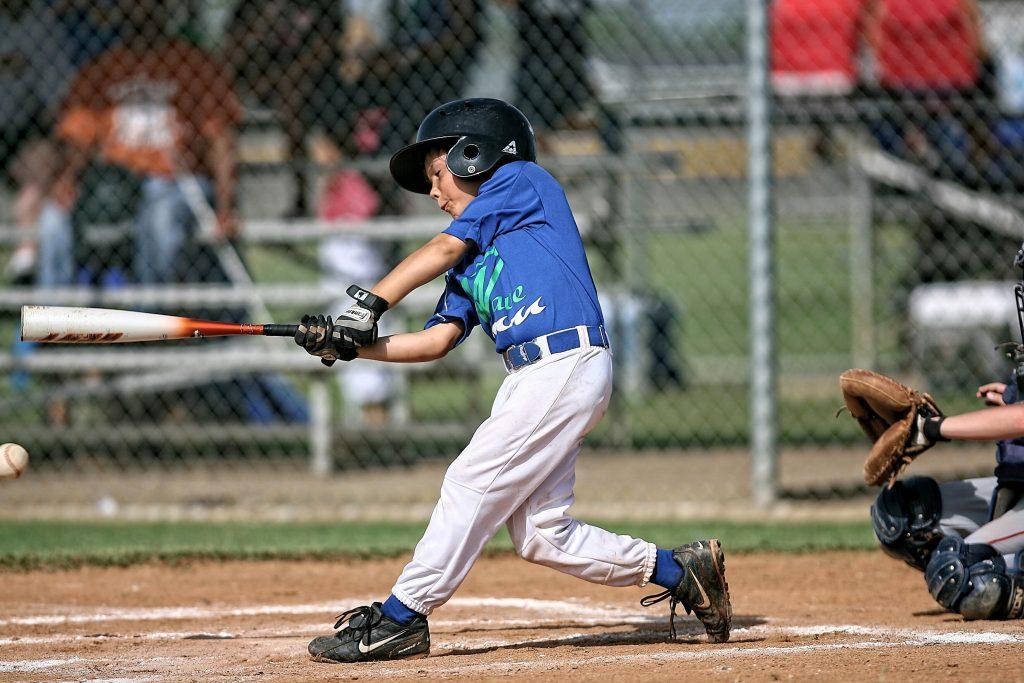 Imagem mostra o momento em que um menino, uniformizado, tenta rebater uma bola de beisebol durante um jogo.