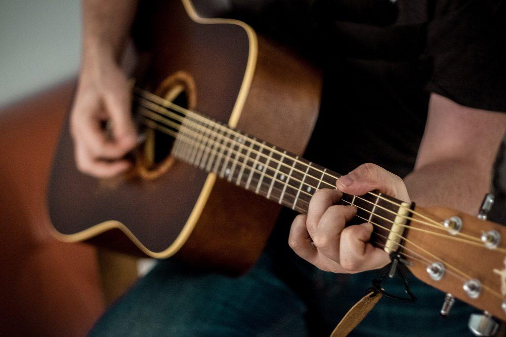 Imagem mostra o close de uma pessoa tocando um violão, com o foco em sua mão esquerda, que faz um acorde no topo do braço do violão.