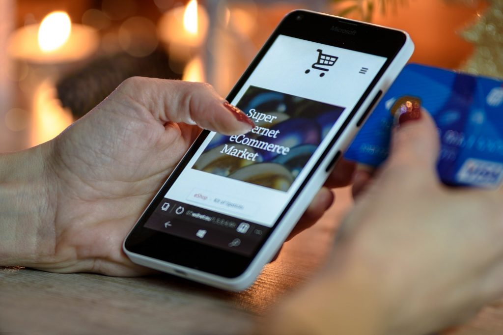 Mão de mulher segurando o celular e o cartão de crédito.