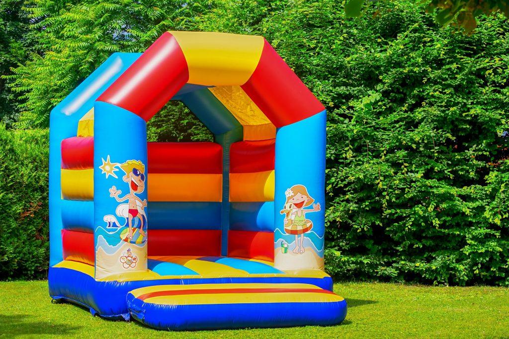 Castelo inflável pequeno sobre gramado em dia ensolarado