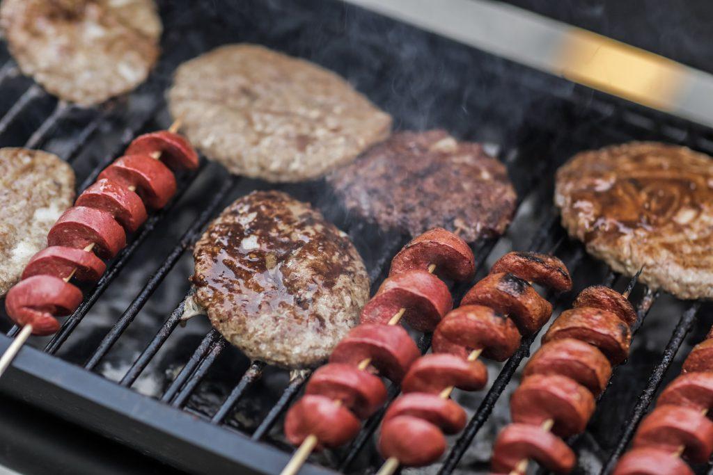Na foto estão hambúrgueres e linguiças assando numa churrasqueira.
