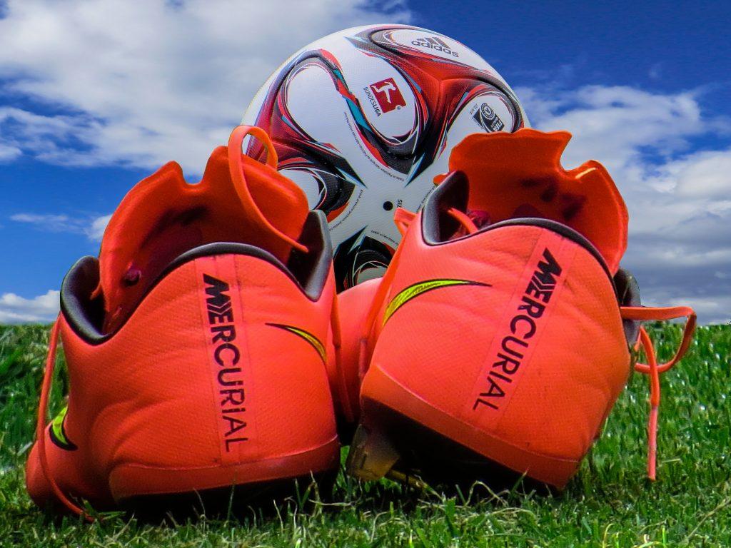 Imagem mostra em plano detalhe a parte traseira de um par de chuteiras Nike Mercurial, apoiada sobre uma grama alta. Ao fundo, uma bola parece estar apoiada nos bicos do par.