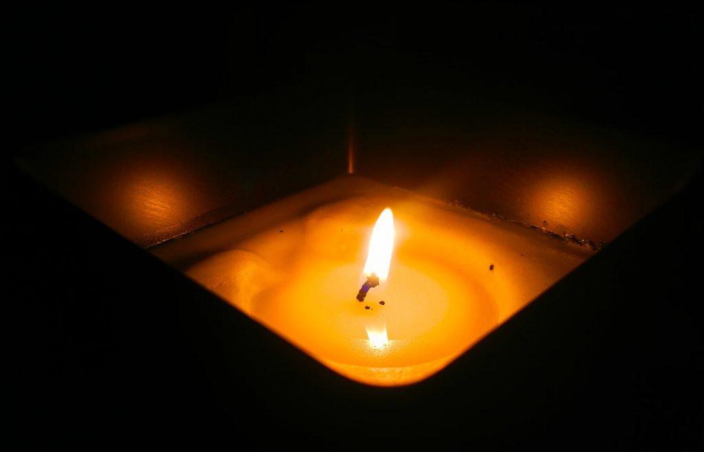 Imagem aproximada de vela de citronela quadrada acesa em fundo escuro