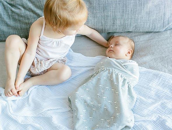 Na foto uma criança ao lado de um bebê dormindo.