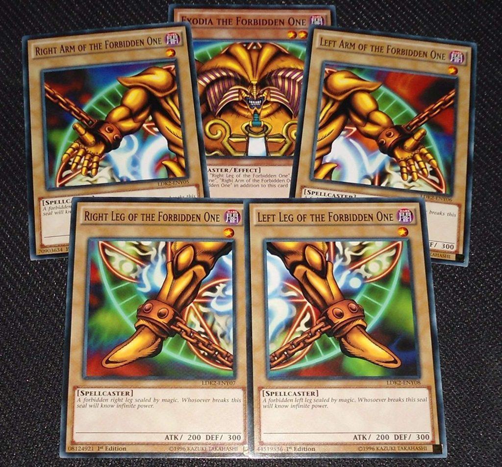 Cinco cartas especiais do deck Yugioh estão sobre uma superfície formando a imagem de um personagem da franquia.