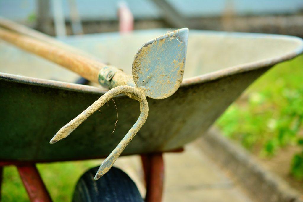 Uma enxada coração em cima de um carrinho de mão em um ambiente natural.