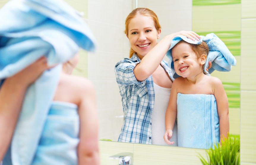 Na foto uma mulher secando os cabelos de uma criança em frente a um espelho dentro do banheiro.