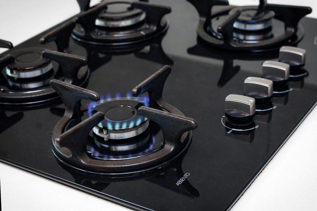 Na foto um fogão com 4 bocas e uma chama acesa.