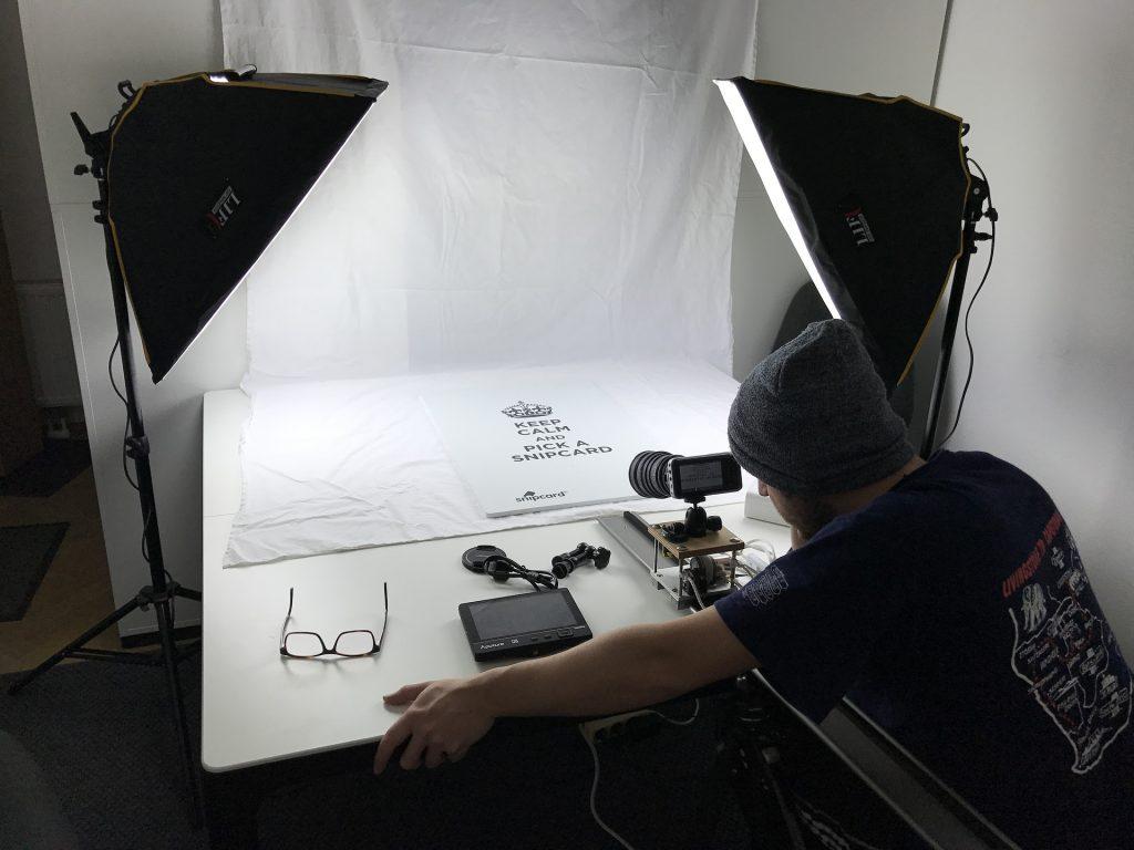 Na foto um homem fazendo fotos em uma mesa.