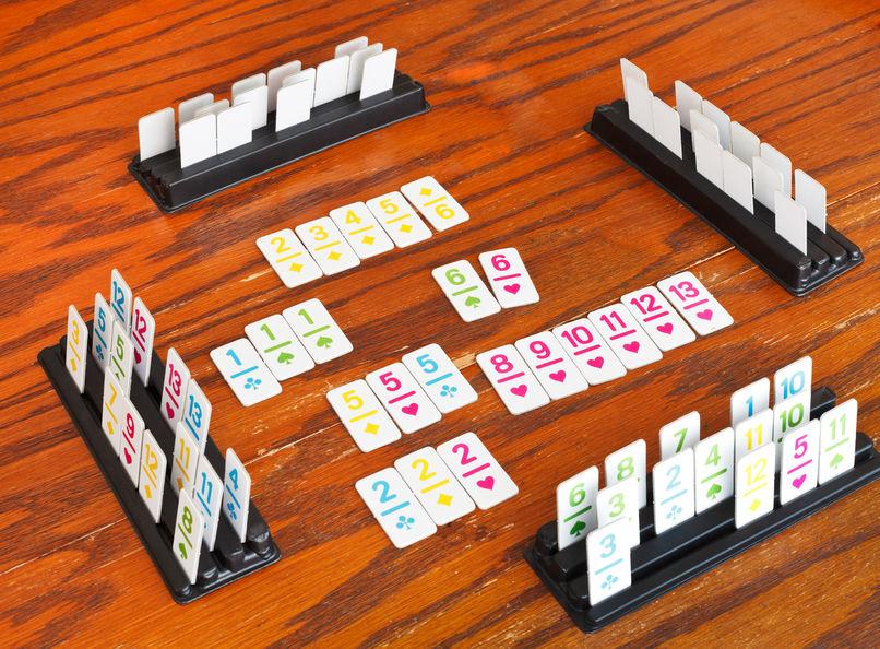 Imagem mostra um jogo de Rummikub montado sobre a mesa, com peças posicionadas nos suportes, e peças dispostas na mesa, ao centro do quadrado formado pelos quatro suportes alinhados.