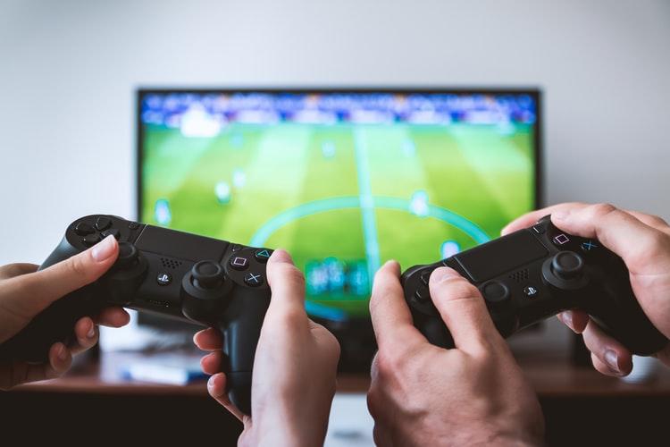 Imagem mostra duas mãos manuseando um controle de PS4, com a tela - desfocada, ao fundo - acessando os menus do console.