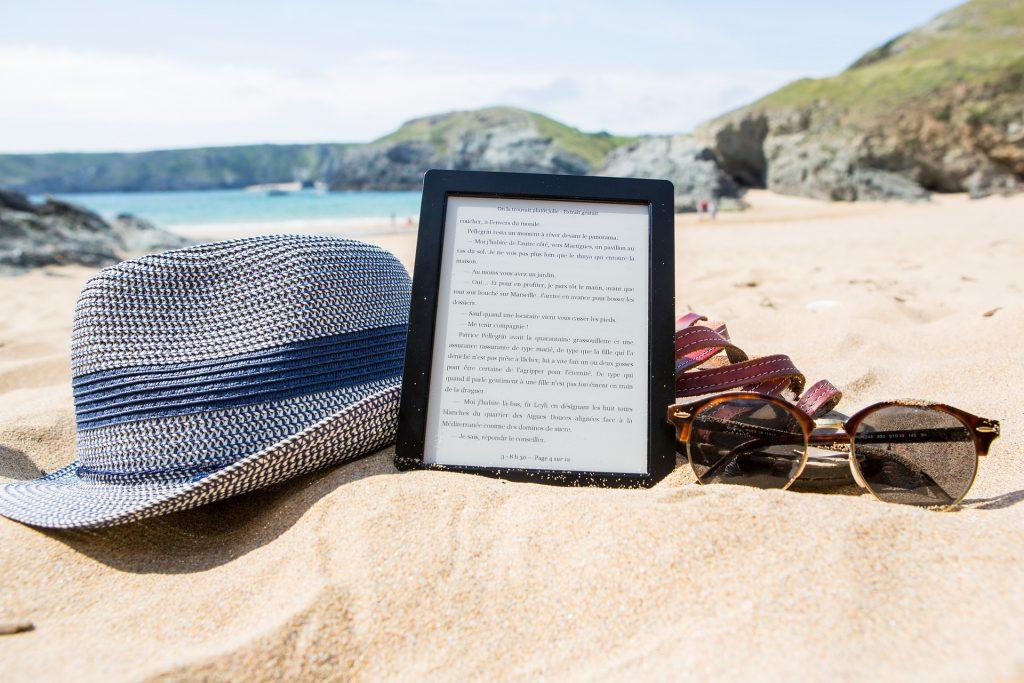 Kindle, chapéu e óculos na areia da praia com o mar ao fundo.