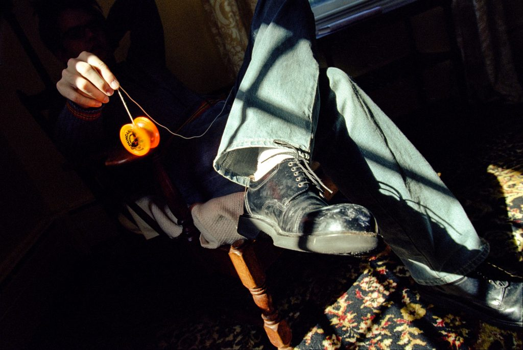 Um homem está sentado de pernas cruzadas em uma cadeira dentro do cômodo de uma casa ou apartamento enquanto segura um ioiô amarelo.