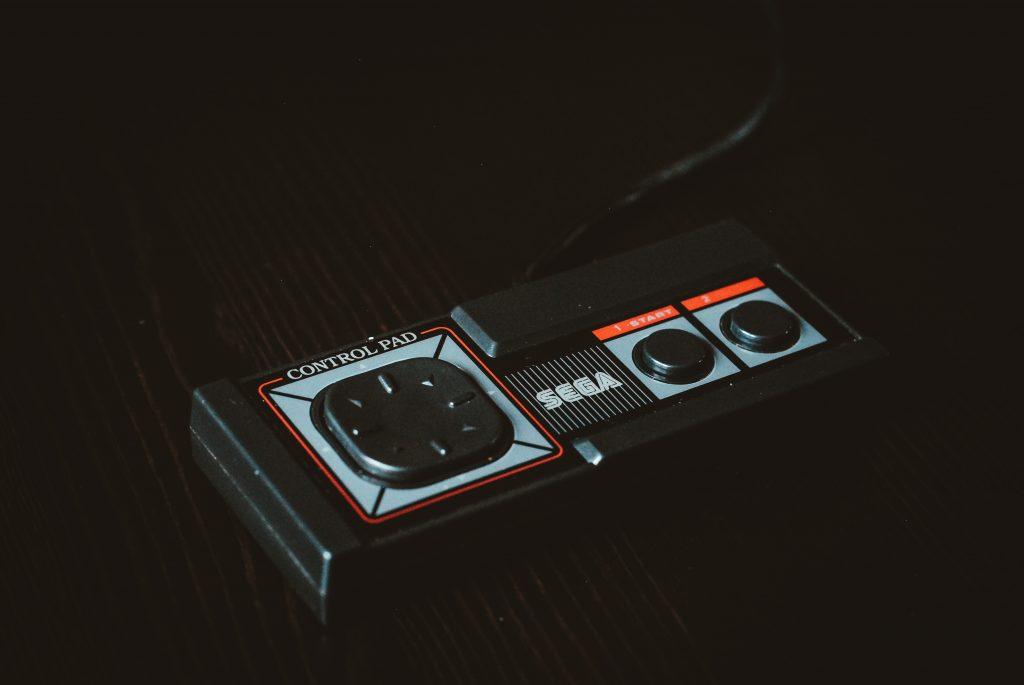 Imagem mostra um controle de um console da Sega sobre uma superfície de madeira.