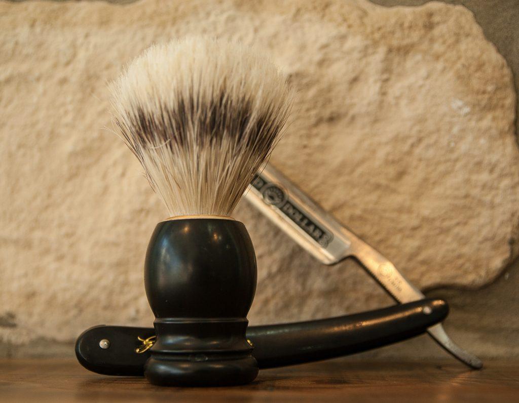 Pincel de barbear com navalha ao fundo