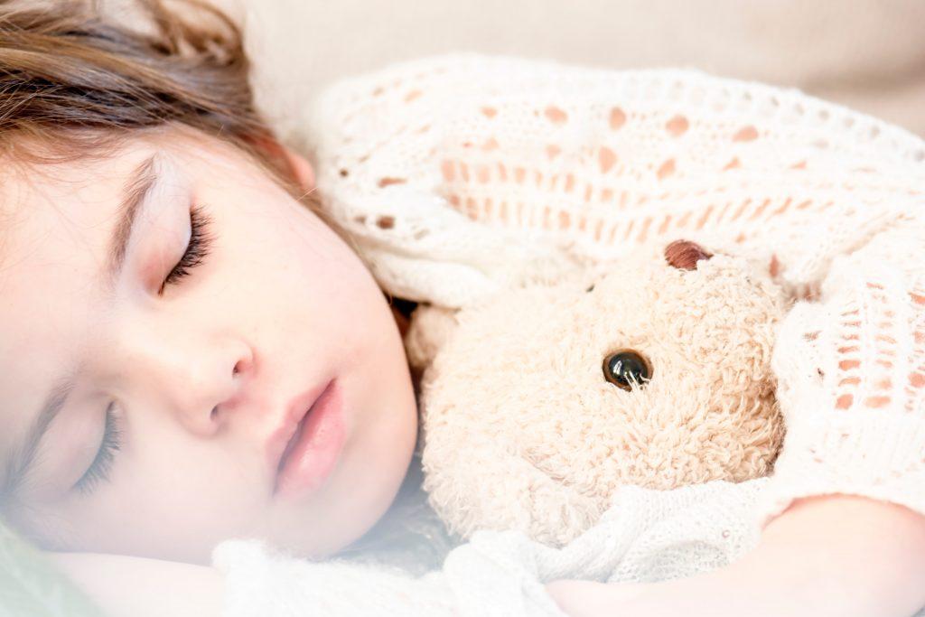 Imagem de uma criança dormindo com uma naninha.
