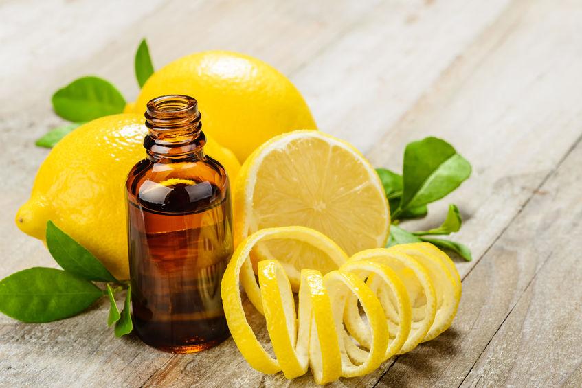 Imagem de óleo de limão ao lado de frutas cortadas e descascadas