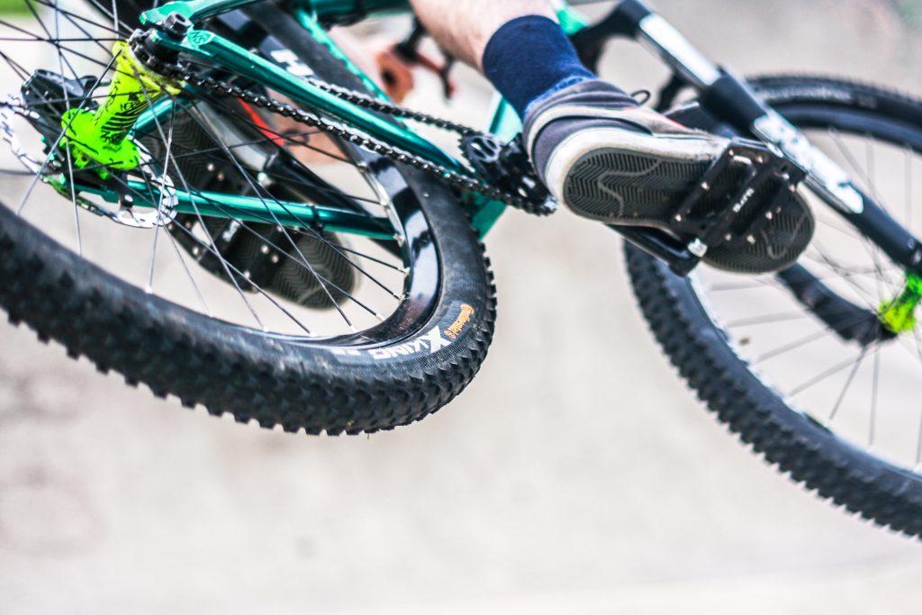 Imagem mostra apenas os pneus e o pedal direito de uma bicicleta durante uma pedalada em alta velocidade.