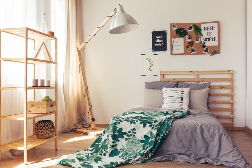 Imagem de quarto feminino com quadro de avisos fixado acima da cama