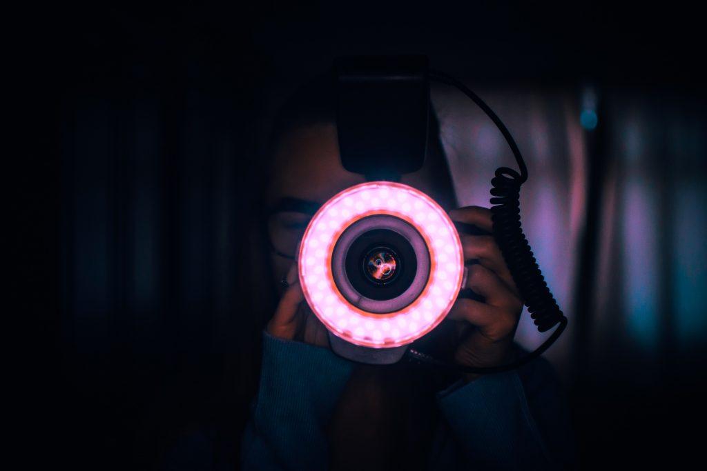 Pessoa fotografando com uma câmera e um ring light.