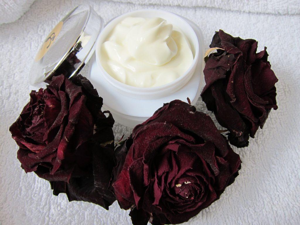 Imagem de pote aberto de creme de ureia cercado por rosas