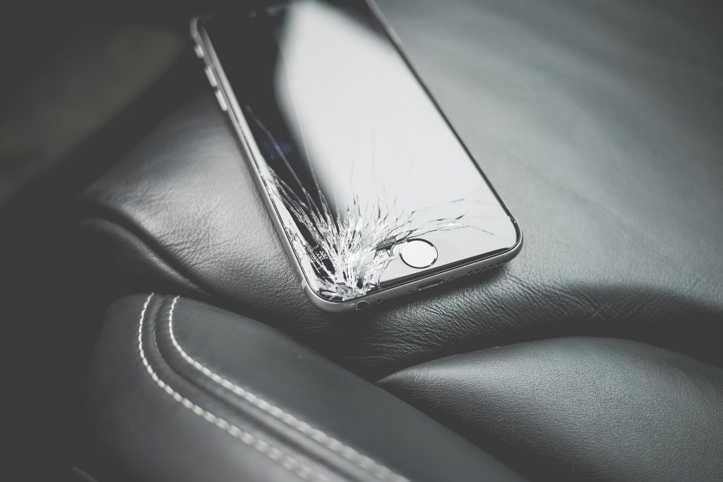 Celular com ponta de tela quebrada sobre banco de couro