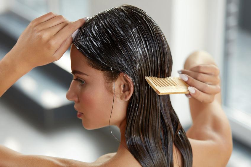 Imagem de uma mulher aplicando um creme no cabelo.