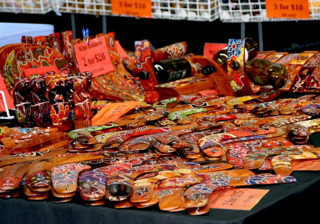 Imagem de banca com vários bumerangues de madeira disponíveis para venda