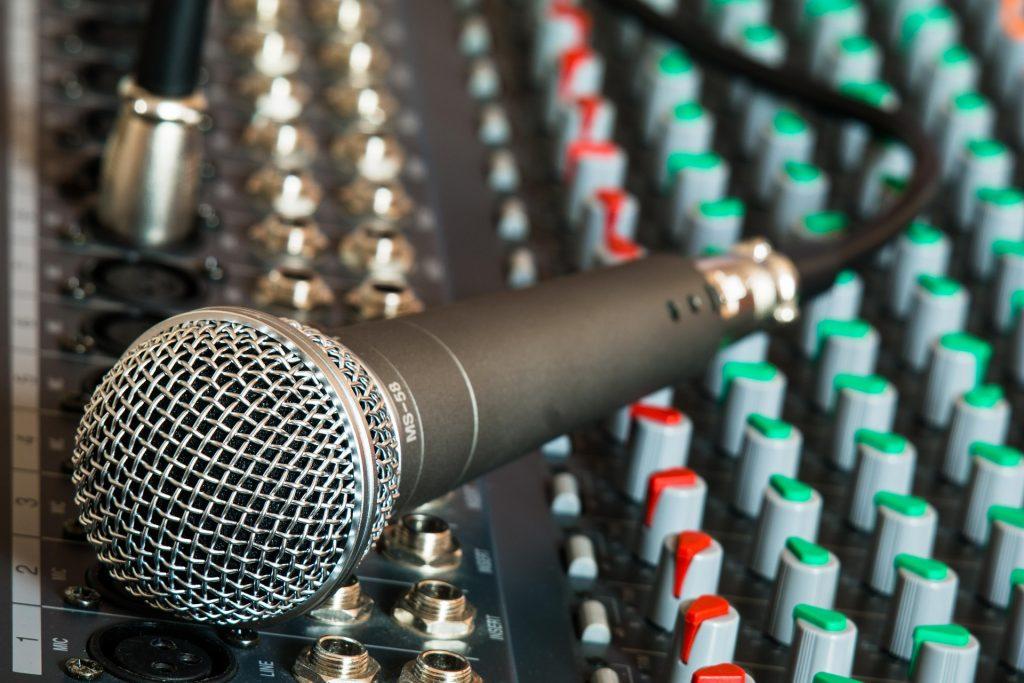 Um microfone conectado a um cabo está em cima de uma mesa de som.