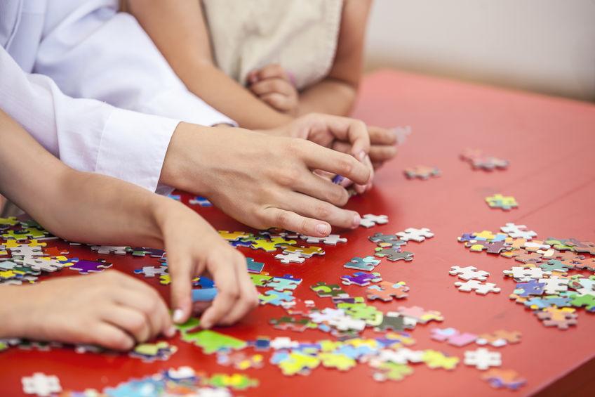 Na foto diversas peças de quebra-cabeças espalhadas com duas crianças e um adulto as manuseando.