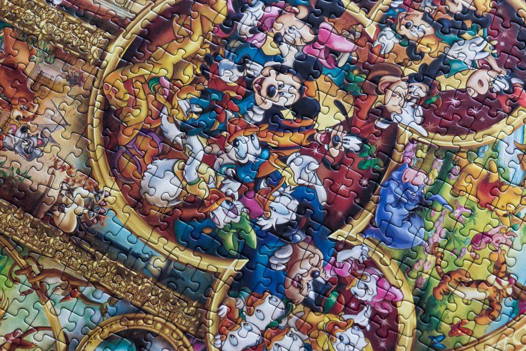 Na foto um quebra-cabeças com o desenho dos personagens do Mickey