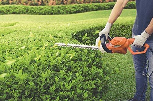 Imagem de um homem utilizando um aparador de cerca viva para cuidar do jardim.