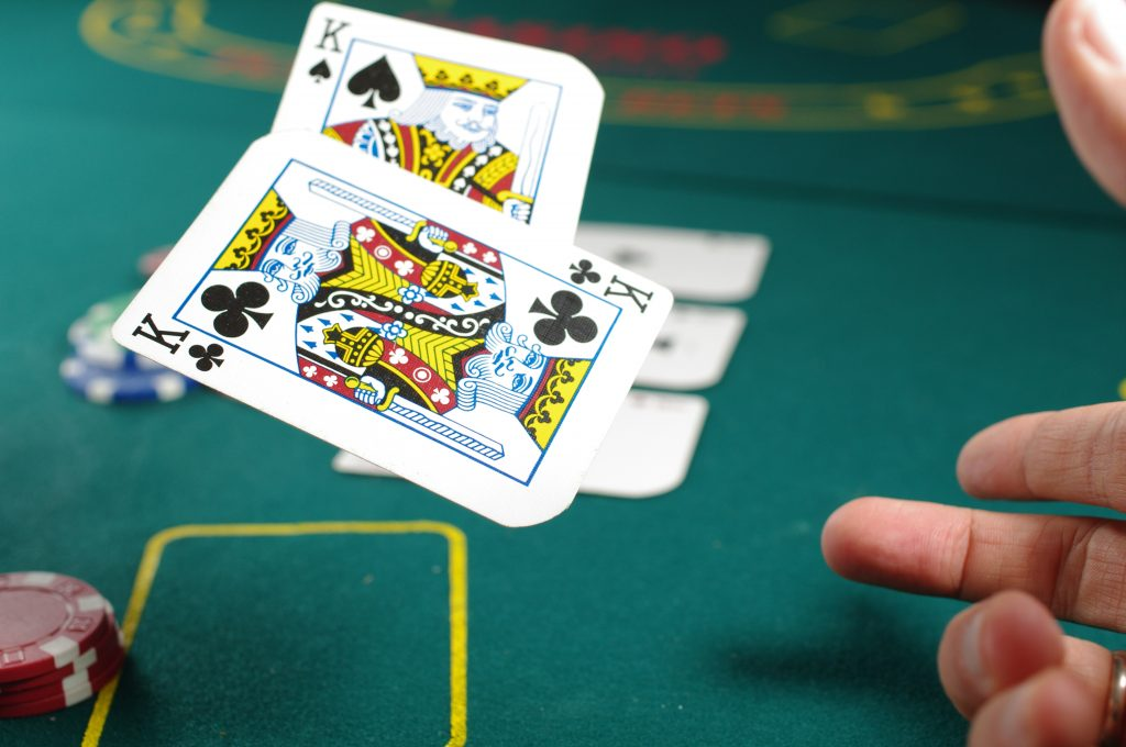 Imagem mostra duas cartas - dois reis - sendo arremessadas sobre uma mesa de poker, durante um jogo.