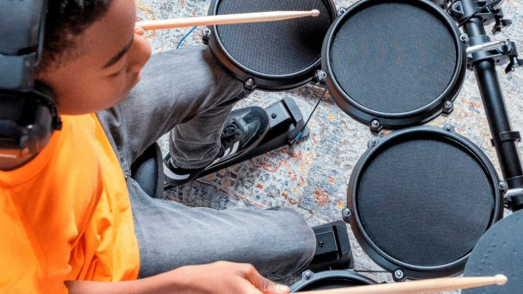 Criança tocando bateria eletrônica, com fone de ouvido.