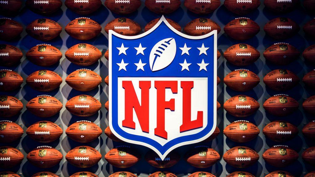 Imagem mostra uma placa com o logotipo da NFL rodeado de bolas de futebol americano, todos expostos numa parede azul.