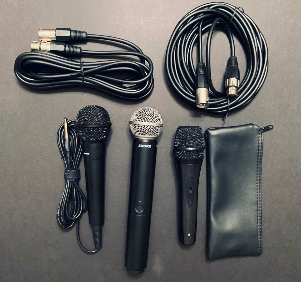 Três microfones (um deles já com um cabo acoplado) e dois cabos XLR estão sobre uma superfície cinza/grafite.