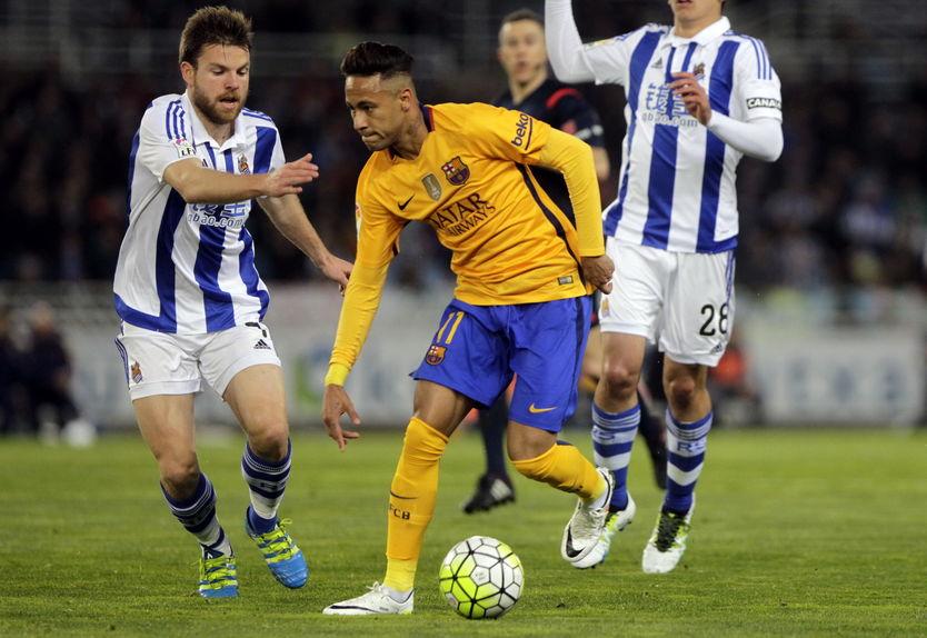 Imagem mostra o momento de um jogo em que Neymar, calçando chuteiras Nike, é marcado por dois adversários.