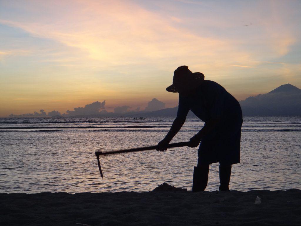 Um homem trabalhando na terra com uma enxada