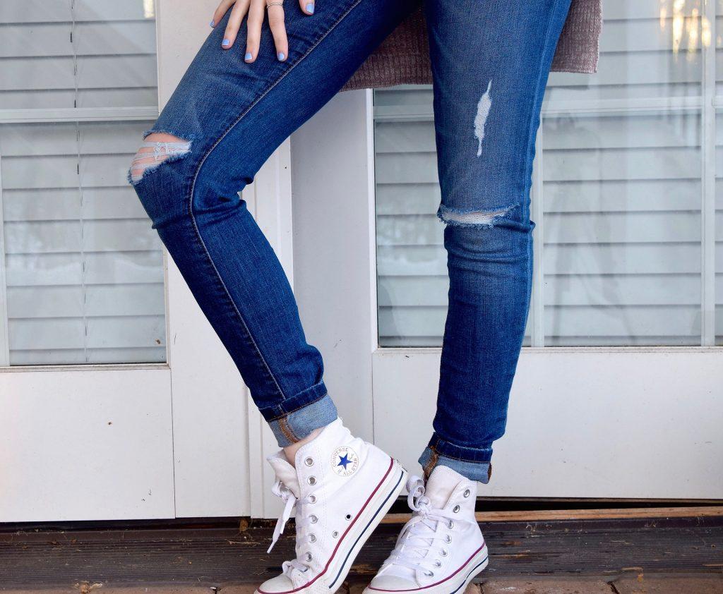 Pernas de uma mulher vestindo calça jeans justa e tênis All Star branco.