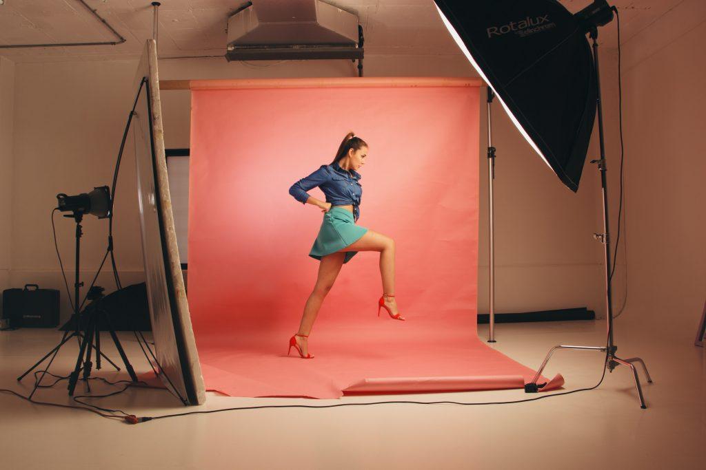 Na foto uma mulher posando em um fundo fotográfico.