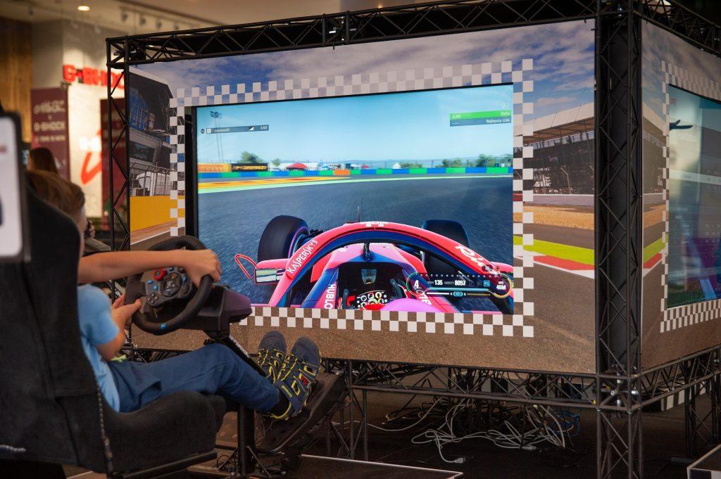 Imagem mostra um menino jogando um simulador de Fórmula 1, com réplicas do banco, volante e pedais.
