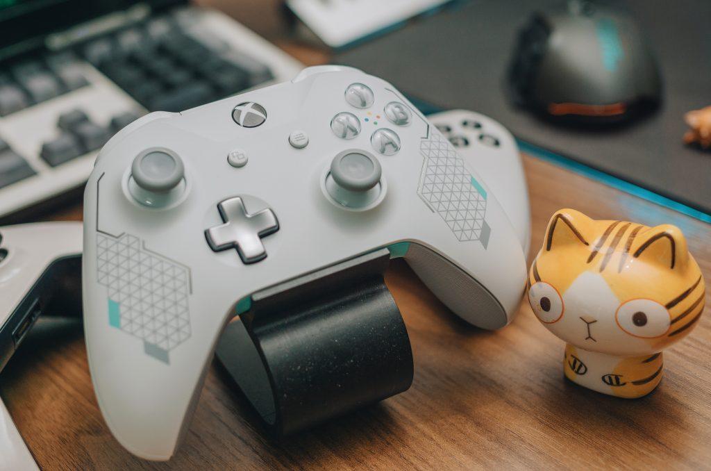 Imagem de controle de Xbox One ao lado de um teclado, mouse e um action figure
