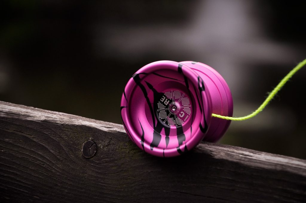 Um ioiô borboleta roxo com detalhes em preto está equilibrado em cima de uma tábua de madeira.