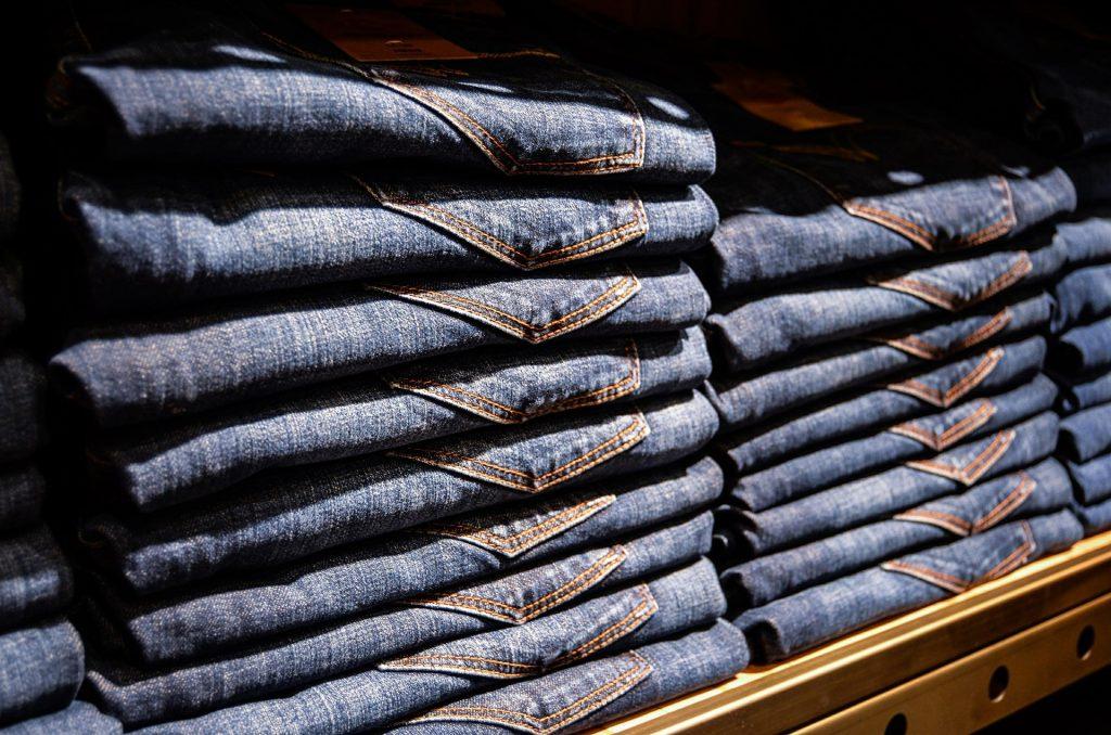 Na foto uma prateleira de loja com algumas calças jeans.