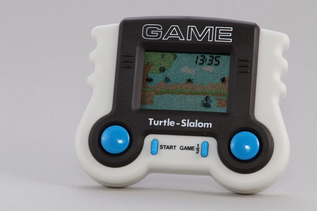 Imagem mostra um mini game infantil, apoiado na vertical, com um jogo rodando em sua tela.