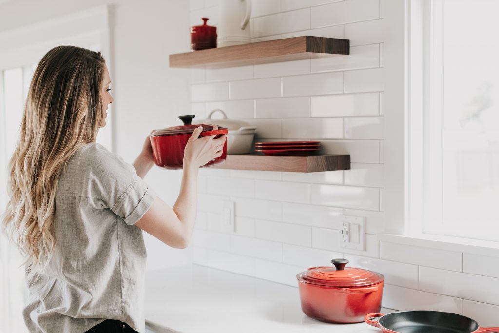 Imagem de uma mulher guardando as panelas.