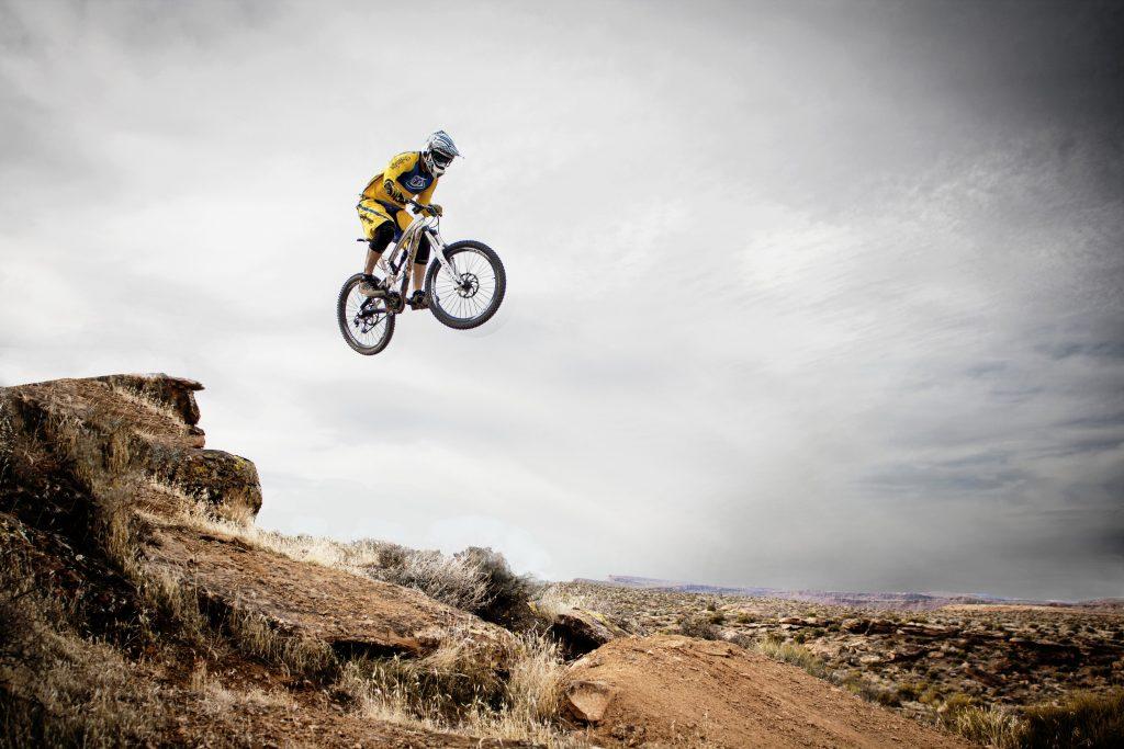 Imagem mostra o momento em que um ciclista salta de uma pedra em uma trilha montanhosa.